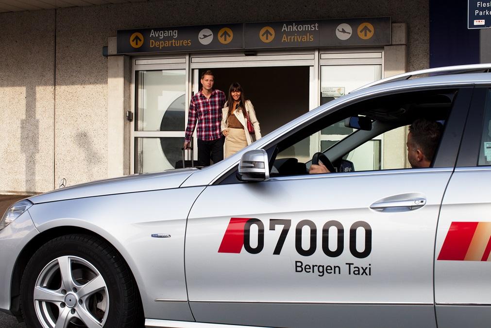 to personer som går ut fra flesland og inn i en taxi